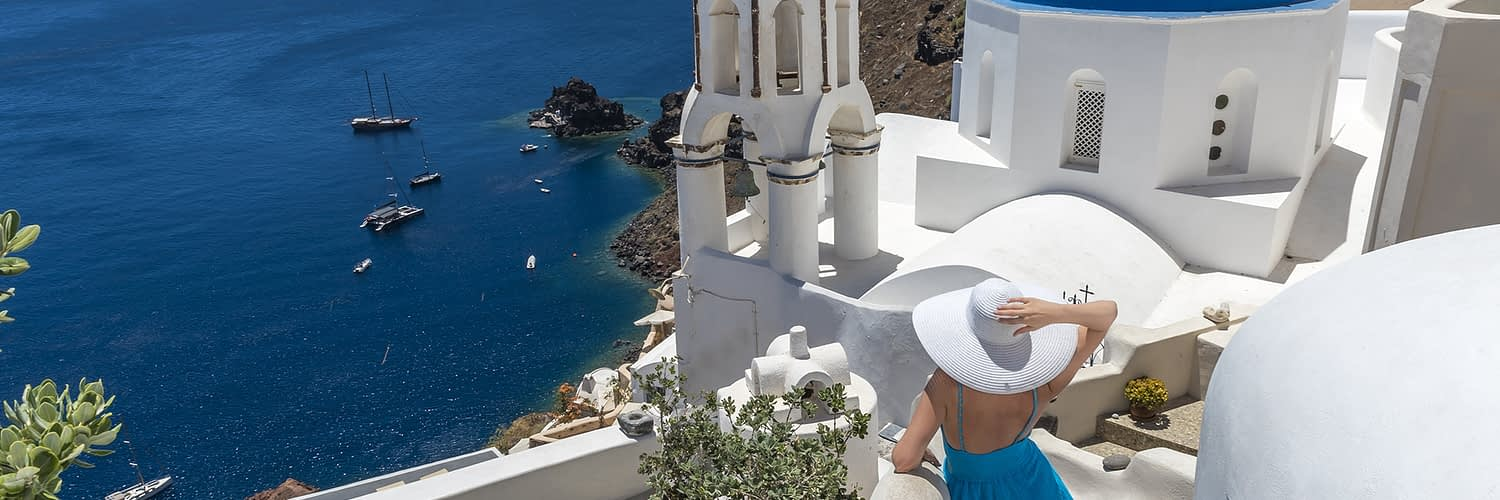 Oia Santorini Greece. Blue domes of Oia. Fashion model. Blue Dress. White Hat.